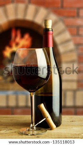bottle and glass of red wine on the background of the rural fireplace - stock photo