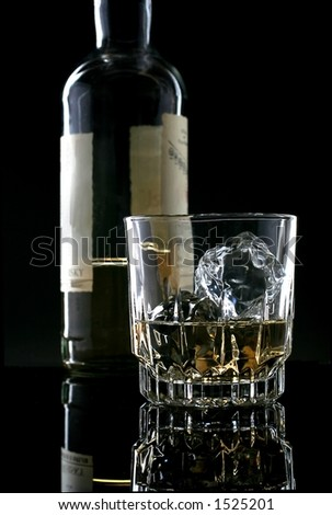 Bottle and glass of whiskey against black background. - stock photo