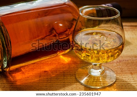 bottle and glass of whiskey  on a wooden background - stock photo