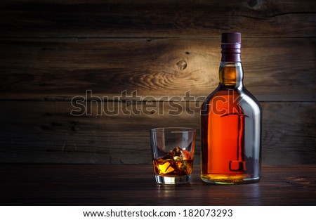 bottle and glass of whiskey with ice on a wooden background - stock photo