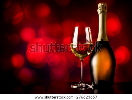 Bottle and glass of white wine on a red background - stock photo