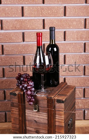 Bottle and glass of wine and ripe grape on box on brick wall background - stock photo
