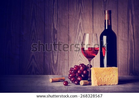 Bottle and glass of wine with cheese grapes and corkscrew on wooden background - stock photo