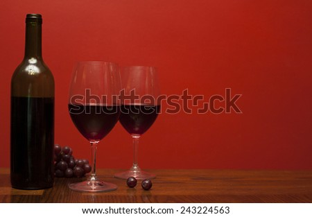 Bottle and glass of wine with red grapes - stock photo