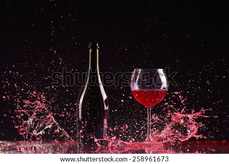 bottle and glass with red wine, red wine splash, wine pouring on table on dark black background, big splash around Glass and bottle of red wine splash on black - stock photo