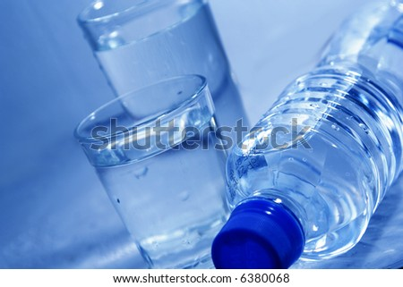 Bottle and glasses of mineral water with droplets - stock photo