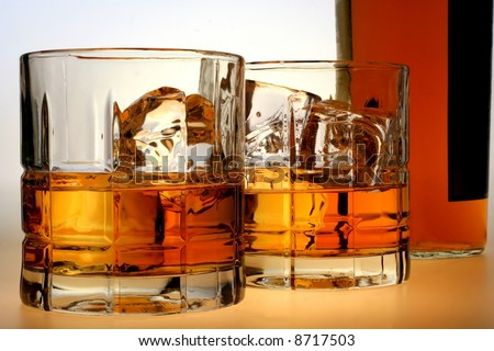 Bottle and glasses of whiskey and ice against white background. - stock photo