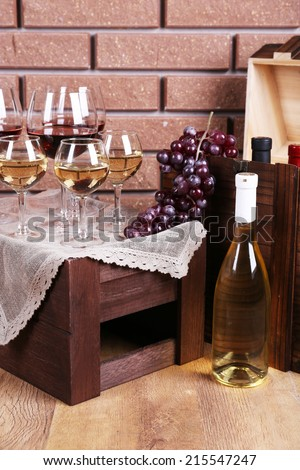Bottle and glasses of wine and ripe grapes on table on brick wall background - stock photo