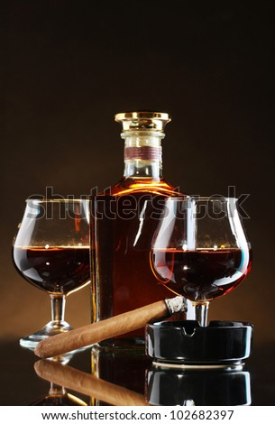 bottle and glasss of brandy and cigar on brown background - stock photo