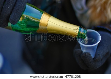 Bottle and plastic glass in the hands - stock photo