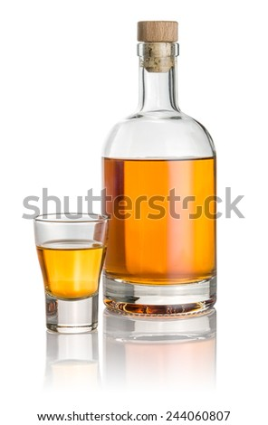Bottle and shot glass filled with amber liquid - stock photo