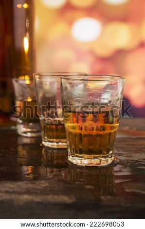 bottle and three glasses of rum whiskey alcohol on wooden table over defocused lights background - stock photo