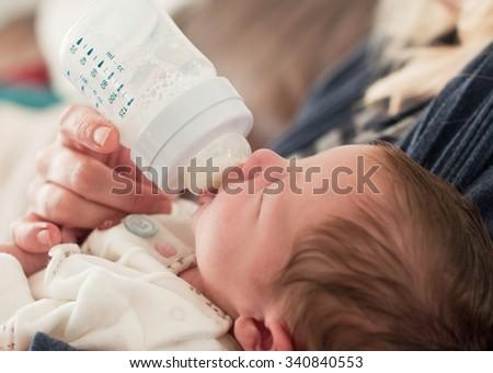 Bottle feeding a baby girl - stock photo