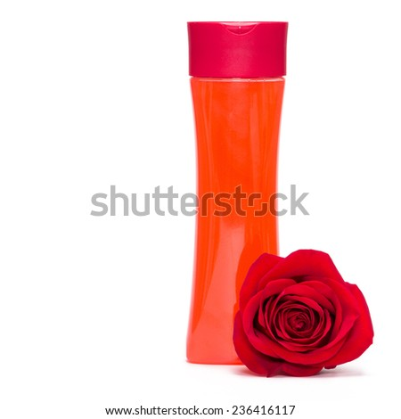 Bottle filled with cleaning cosmetics and red rose on white background - stock photo