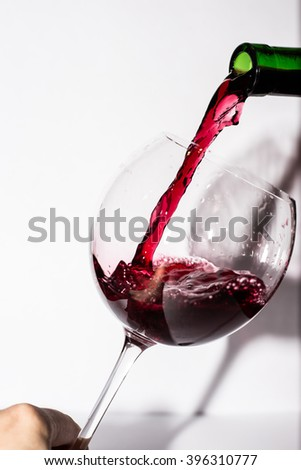 Bottle filling the glass of red wine - stock photo