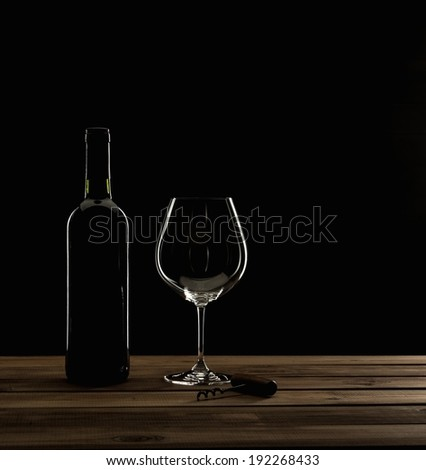 Bottle,glass and corkscrew on a wooden table  - stock photo