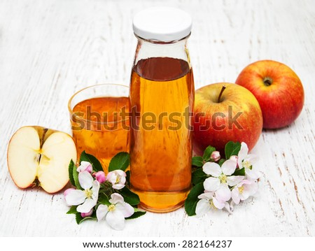 Bottle of apple juice with apples and flowers on a wooden background - stock photo