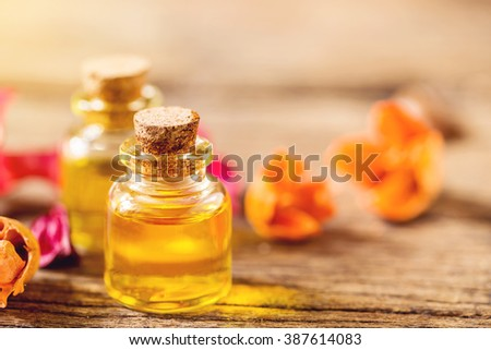bottle of aroma essential oil and dry flower on wooden floor, spa concept. - stock photo