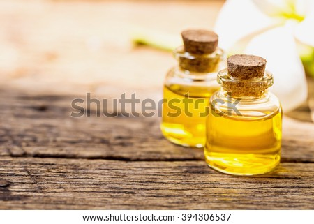 bottle of aroma essential oil or spa and natural fragrance oil with dry flower on wooden table, image for aroma spa alternative therapy medicine and meditation aroma concept. - stock photo