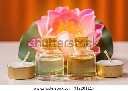 bottle of aroma essential oil with candle and pink lotus on stone table, spa concept. - stock photo