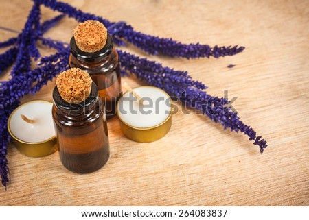 bottle of aroma essential oil with grass flower and candle on wooden background, spa concept. - stock photo
