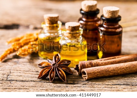 bottle of aroma essential oil with star anise with cinnamon stick with dry flower on  on grunge wooden table , spa  and alternative medical concept. - stock photo