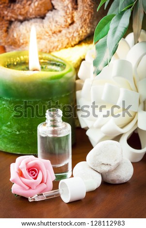 Bottle of aromatherapy oil and candle. - stock photo