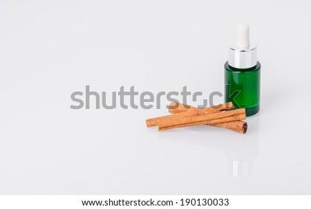 Bottle of aromatic oil and cinnamon sticks - stock photo
