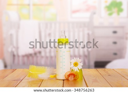 bottle of baby milk on the table in the nursery - stock photo