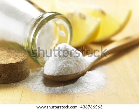 bottle of baking soda with wooden spoon - stock photo