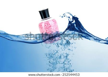 Bottle of bath salt in water - stock photo