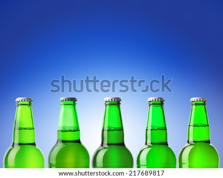bottle of beer green on a blue background - stock photo