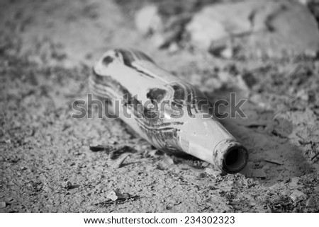 bottle of beer in the mud in black and white - stock photo