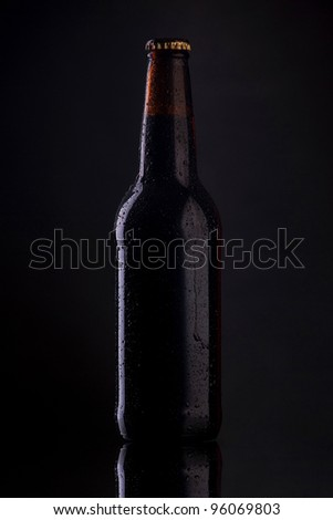 Bottle of beer with drops on dark background. - stock photo