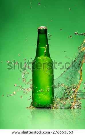 Bottle of beer with splash around on green background. - stock photo