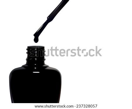 Bottle of black nail polish and drop isolated on white background - stock photo