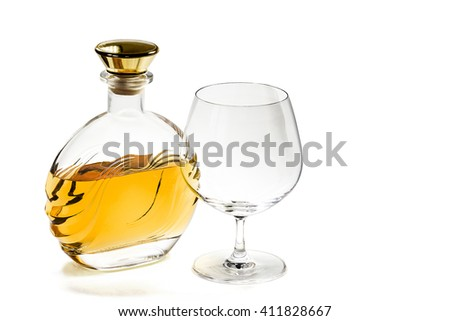 Bottle of brandy and empty snifter on white background - stock photo