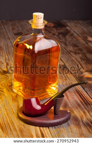 Bottle of brandy and tobacco pipe on a wooden table - stock photo