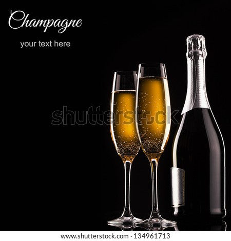 bottle of champagne and glasses over dark background - stock photo