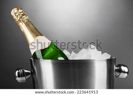 Bottle of champagne in bucket with ice, on grey background - stock photo