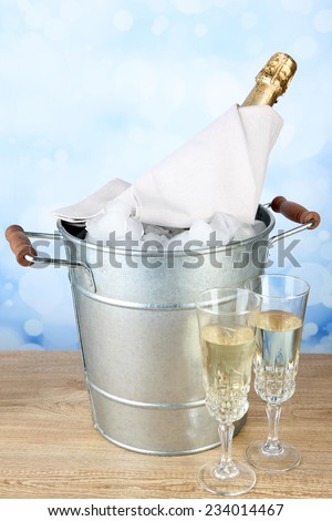 Bottle of champagne in metal ice bucket and two glasses on wooden table on light background - stock photo
