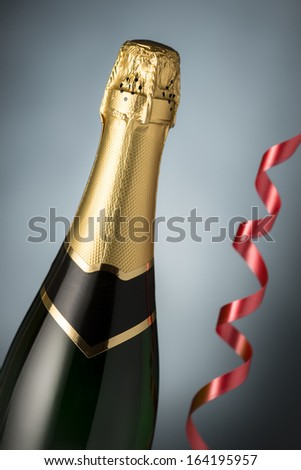 Bottle of champagne, serpentine  closeup. Celebration. New Year Card Design with Champagne. Christmas Scene.  - stock photo