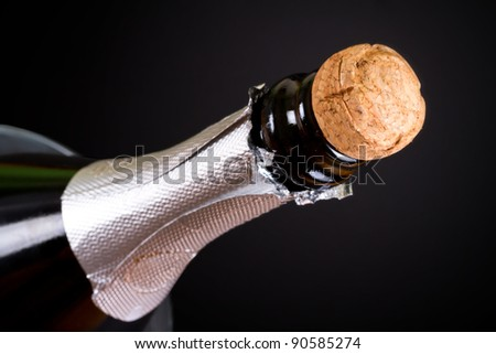 Bottle of champagne with cork over black background - stock photo
