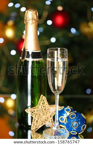 Bottle of champagne with glass and Christmas balls on Christmas tree background - stock photo