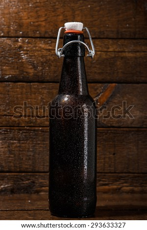 Bottle of cold beer over wooden background - stock photo