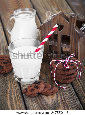 Bottle of cold milk with paper tube, chocolate cookies on wooden background - stock photo