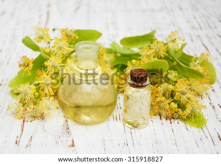 bottle of essential linden oil and yellow lime flowers - stock photo