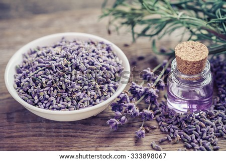 Bottle of essential oil and lavender flowers in bowl and on table. Selective focus. - stock photo
