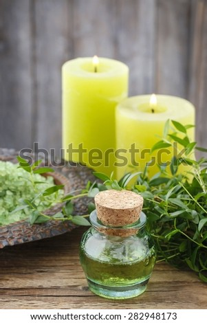 Bottle of essential oil, bowl of green sea salt and scented candles - stock photo
