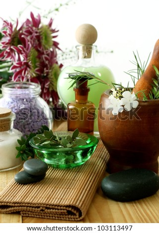 Bottle of essential oil, stones,  mortar and flowers - stock photo